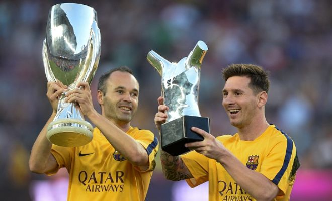Lionel Messi lifts up his UEFA Best Player in Europe Award past Barcelona's midfielder Andres Iniesta holding the UEFA Supercup before the game.