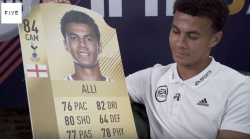 Dele Alli on Rio Ferdinand's YouTube channel, holding his rating card