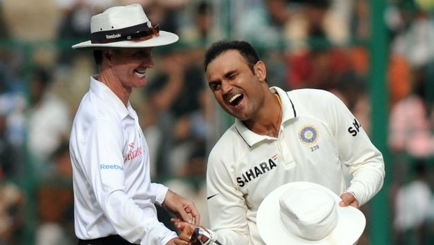 Sehwag enjoys a light moment with umpire Billy Bowden