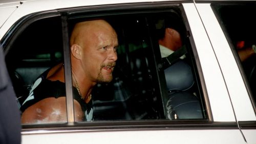 Stone Cold being carted away in a police car