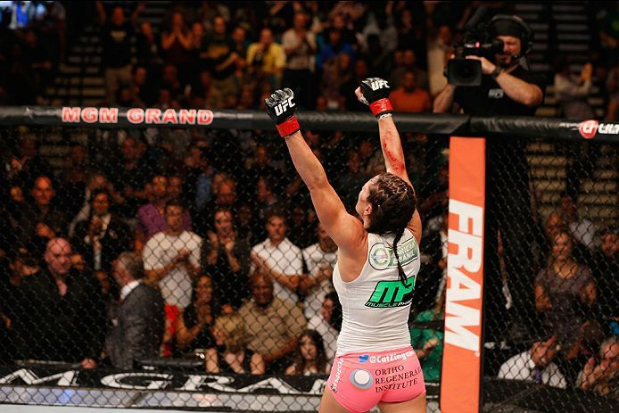 Zingano raises her arms in victory