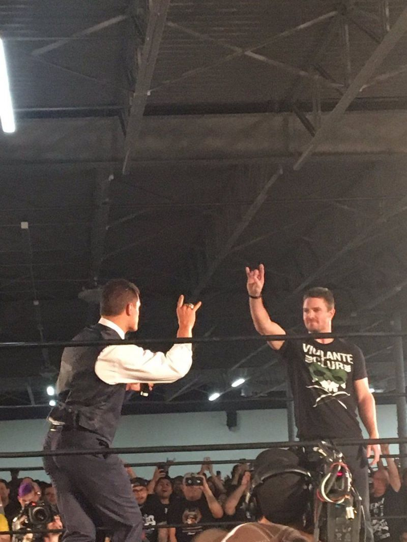 Stephen Amell doing the Too Sweet gesture with Cody Rhodes