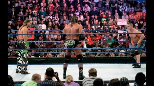 Shawn Michaels, Triple H, and John Cena squaring-off in a WWE ring
