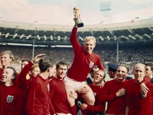 Sport Football. pic: 30th July 1966. 1966 World Cup Final at Wembley. England 4 v West Germany 2 a.e.t. England captain Bobby Moore holds aloft the World Cup (Jules Rimet trophy) as the team gather around to celebrate.
