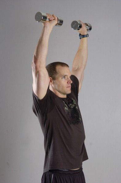 (GA) ---FE17FTWEIGHTS-- Lee Cherry, exercise physiologist with Strength from Within LLC demonstrates proper standing dumbbell press keeping your gaze forward and stay relatively still and exhale while lifting the weights. Glenn Asakawa / The Denver Post