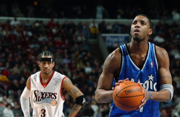 Tracy McGrady shoots as Iverson looks on