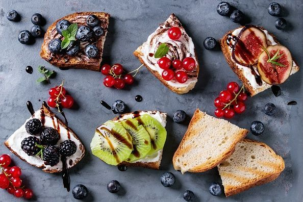 Variety of dessert sandwiches with berries and cream cheese and chocolate swirl. Red currant, blueberries, sliced kiwi, figs over gray metal background. Flat lay, summer appetizer concept