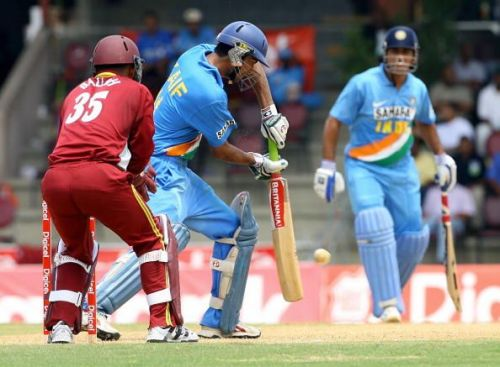 Indian batsman Mohammad Kaif (C) slams a