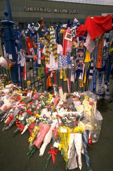 Floral tributes and scarves adorn a fence