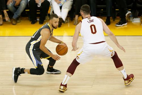 Curry dribbles past Kevin Love