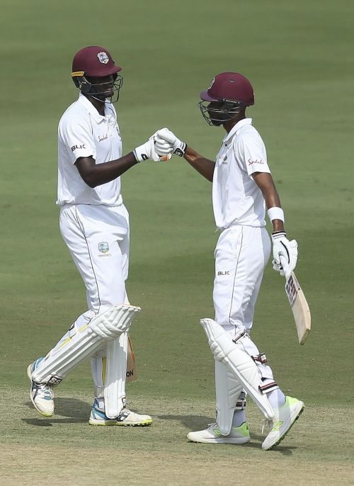 Chase and Holder congratulating each other after a century partnership