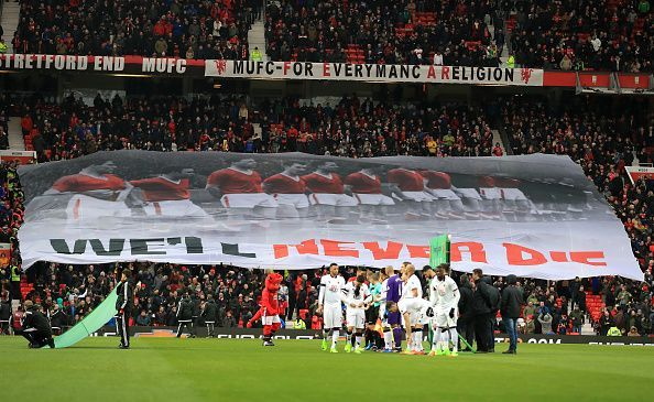 The Stretford End holding up a tifo of the Busby Babes