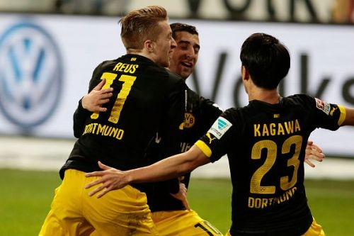 Dortmund players celebrate a goal in the match against Wolfsburg in the Bundesliga