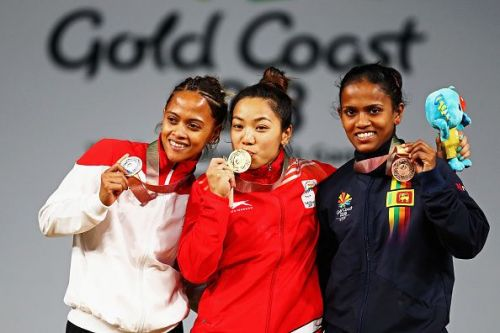 Mirabai Chanu (centre) celebrates on the podium at the Commonwealth Games 2018