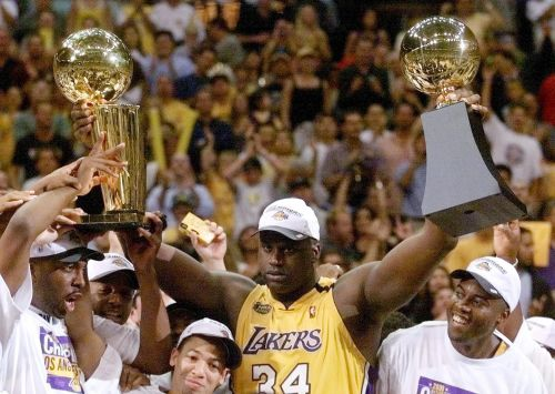 Shaquille O'Neal with the Finals MVP trophy and Larry O'Brien trophy