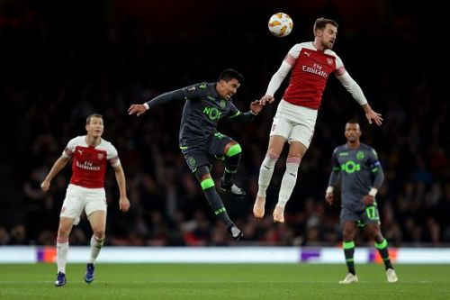 Aaron Ramsey tussling for possession in the air during Arsenal's Group E home clash against Sporting