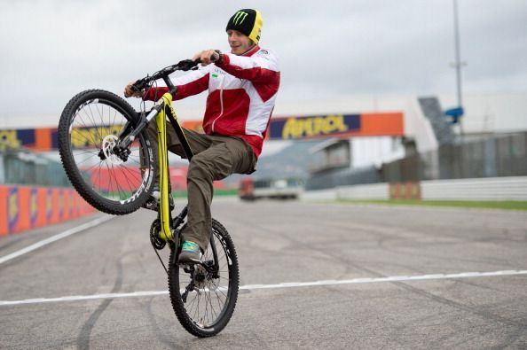 Valentino Rossi pulling off a wheelie with his bicycle at the MotoGP of San Marino