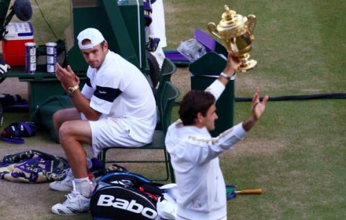 A dejected Roddick looks on as Roger Federer celebrates his 6th Wimbledon Championships win