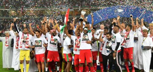 Omani players and staff celebrate after lifting the Arabian Gulf Cup in January 2018