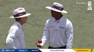 Umpires discussing after referring to the TV umpire with a soft signal