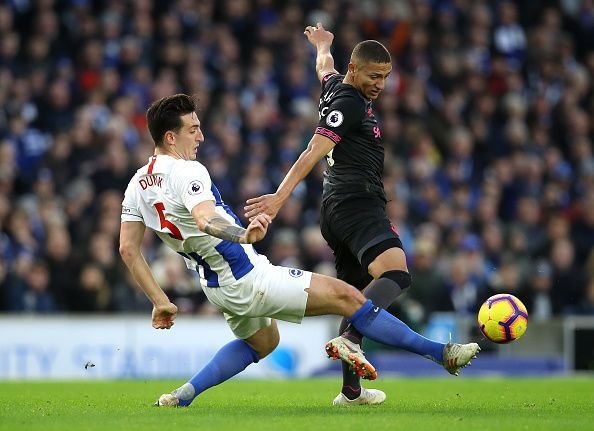 Lewis Dunk tackling Everton attacker Richarlison