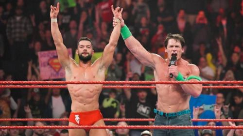 John Cena raises Finn Balor's hand in victory on RAW.