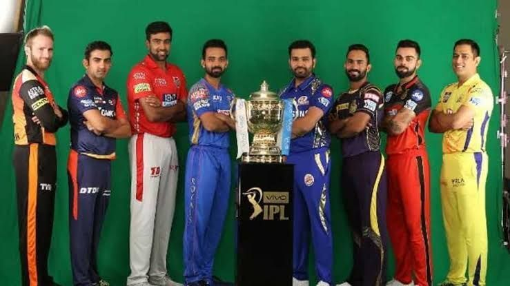 8 franchise captains of the IPL stand in with the IPL trophy in the middle.
