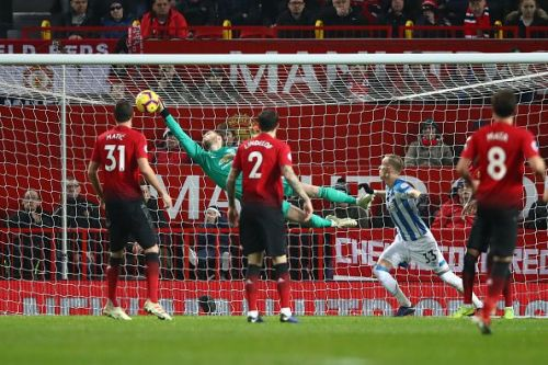 De Gea makes a save during a Huddersfield Town match, as Matic and Lindelof look on.