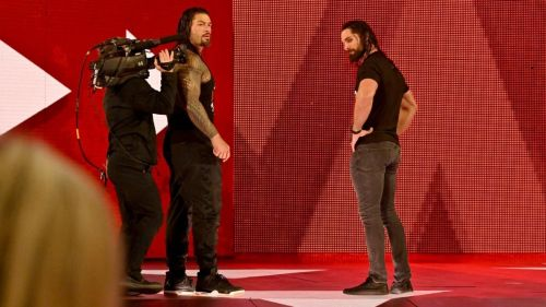 Roman Reigns and Seth Rollins looking at a fallen Dean Ambrose!