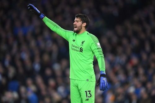 Alisson Becker plays against Brighton & Hove Albion in a Premier League game.