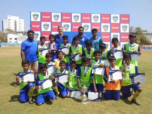 Players of Anjuman Matriculation with Chennaiyin FC coach John Gregory and player Dhanpal Ganesh after winning the Boost Chennaiyin FC Football Championship (U-13)