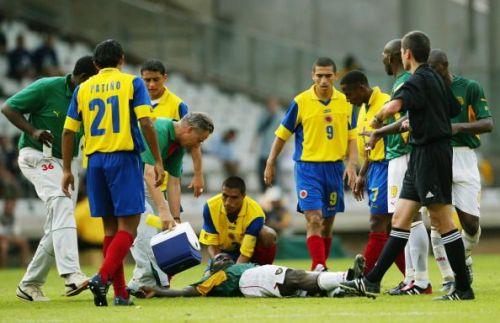Marc-Vivien Foe of Cameroon is helped by Colombian captain Ivan Cordoba
