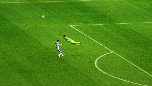 Manuel Neuer flying to head the ball away from danger in a counter-attack.