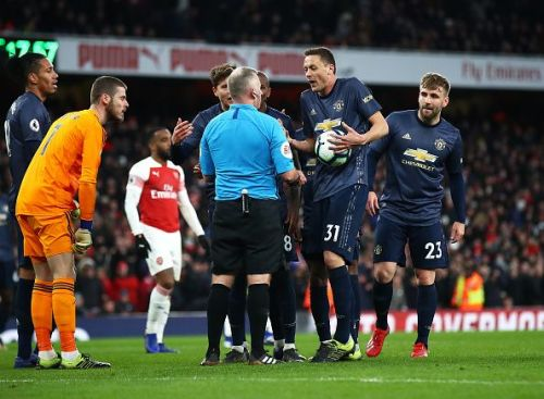 Manchester United players protesting against the penalty decision.