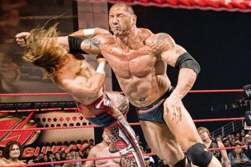 The Animal Batista floors Edge with a clothesline...or is it a lariat?