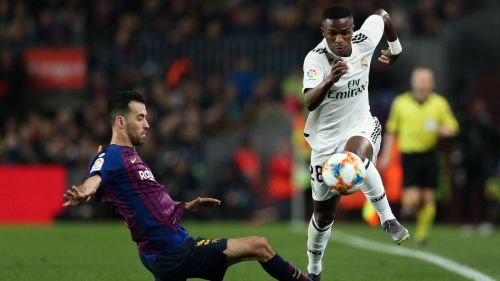 Vinicius Junior competes for the ball with Sergio Busquets