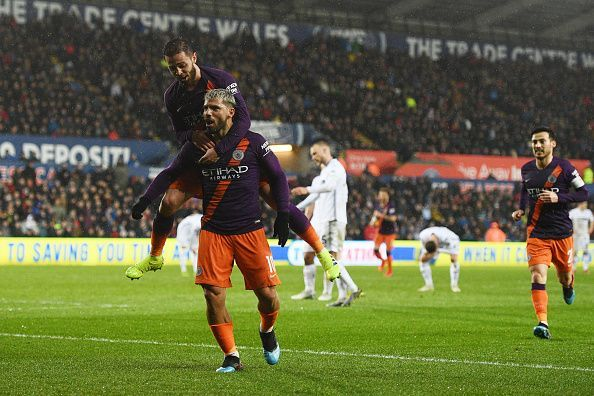 Aguero celebrates with both Bernardo and David Silva during City's 3-2 away win vs. Swansea