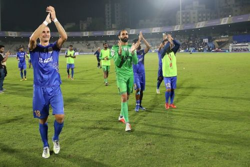 Mumbai City players Lucian Goian and Amrinder Singh celebrate after the team booked their berth in the ISL playoffs