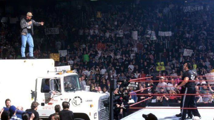 Stone Cold on top of a beer truck before spraying The Rock and The McMah