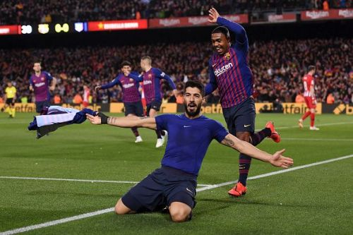 Suarez wheels away to celebrate Barca's first goal against ten-man Atletico Madrid