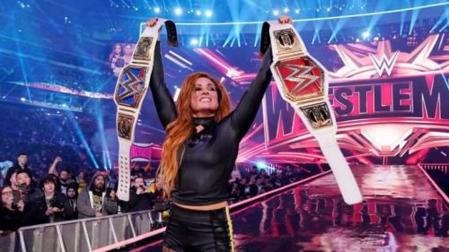 Becky Lynch proudly hefts both the Raw and Smackdown women's championships.
