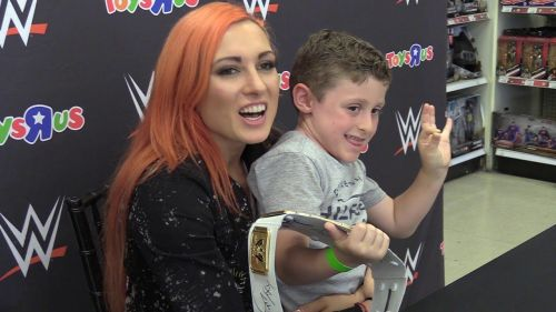 Becky Lynch with a young male fan. Lynch's popularity transcends age, race, and gender.