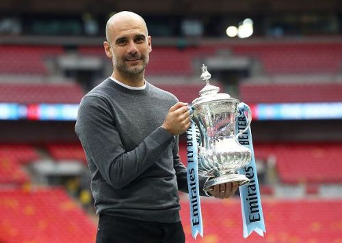 Manchester City's Pep Guardiola holds the FA Cup.