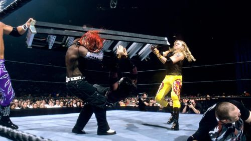 Edge and Christian smash Jeff Hardy with a ladder while Bubba Ray Dudley recovers during the first TLC match.