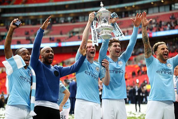 Manchester City players celebrate with the FA Cup trophy aloft after their emphatic win over Watford