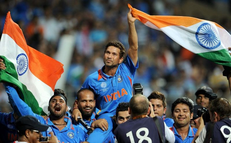 Sachin Tendulkar, carried by his teammates waves the Indian flag after India won the 2019 Cricket World Cup final in Mumbai on 02 April 2011 (© William West, AFP/Getty Images).