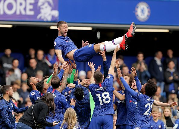 Gary Cahill lifted up by his teammates during Chelsea