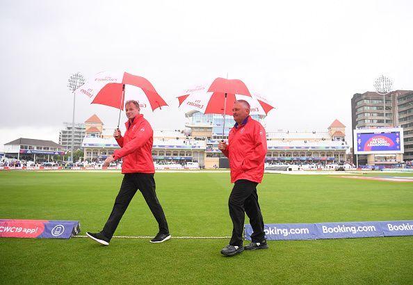 Umpires Paul Reifel and Marais Erasmus take cover under umbrellas in a gloomy Trent Bridge stadium on Thursday.