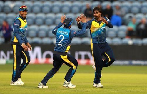 Nuwan Pradeep (right) celebrates the fall of a wicket.