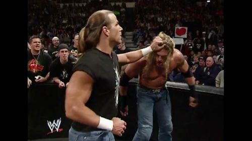 HBK measures Edge for a brutal closed fist blow.